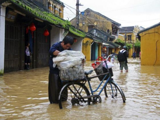 A man transporting rice cakes for sale on his bicycle, looks at his produce while standing on a flooded street in Vietnam's central ancient town of Hoi An on Nov 18, 2013. Photo: Reuters