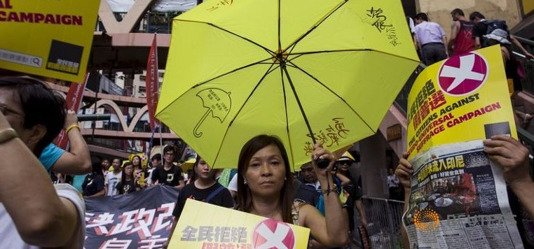 A pro-democracy protester holds a yellow umbrella, the symbol of the Occupy Central movement, during a march to demand lawmakers reject a Beijing-vetted electoral reform package for the city's first direct chief executive election in Hong Kong, China on June 14, 2015