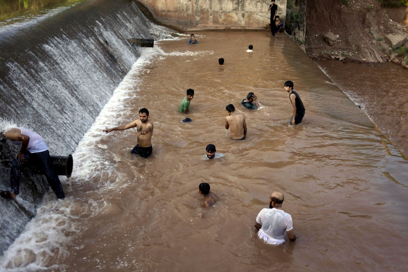 Pakistani youths cool off themselves at a river on the outskirts of Islamabad, Pakistan, Sunday, June 21, 2015. Photo: AP