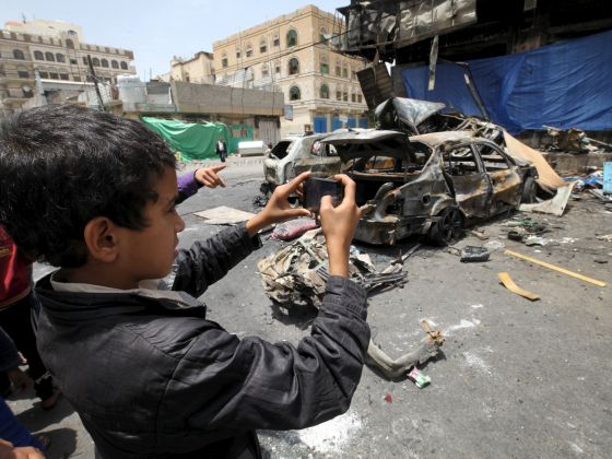 Boy takes pictures for the wreckage of a car at the site of a car bomb attack in Yemen's capital Sanaa. Photo: Reuters