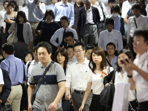 Commuters walk through a train station during a morning rush hour in Tokyo. Photo: AP