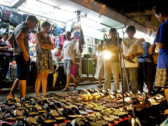 Tourists walk through a street market on Sukhumvit Road in Bangkok, Thailand, on Aug 2, 2010. Photo: Bloomberg