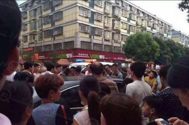 A large crowd gathering around the BMW, which held the trapped toddler. PHOTO: FACEBOOK/CCTVNEWS.