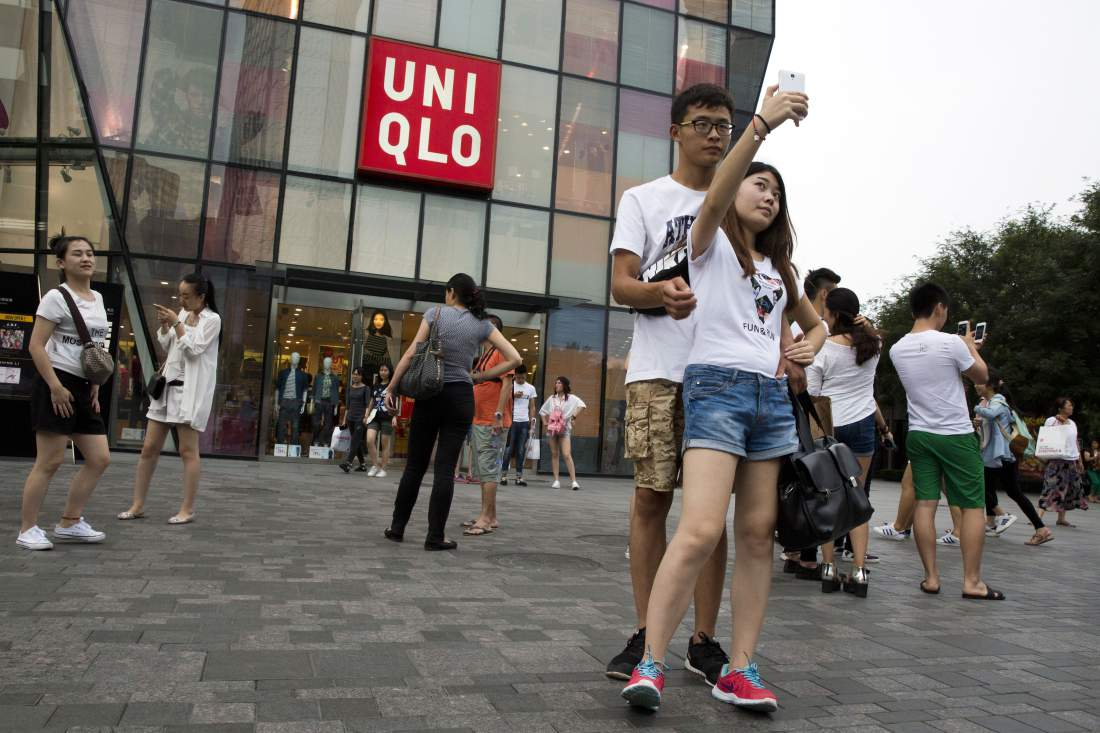 A Chinese couple take a selfie outside the Uniqlo flagship store where a steamy video purportedly taken inside one of its fitting room showing a couple apparently having sex in Beijing, Thursday, July 16, 2015. While online searches for the Japanese clothing brand soared after the viral spread of the video, it has also drawn the concern of the police and China's highest web regulator who are investigating whether it was a vulgar marketing gimmick. (AP Photo/Ng Han Guan)