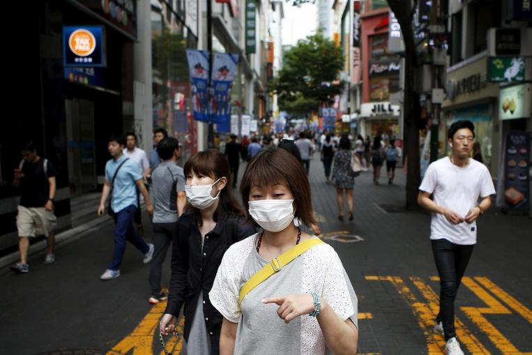 People wearing masks in Seoul's Myeongdong shopping district on July 9. PHOTO: REUTERS