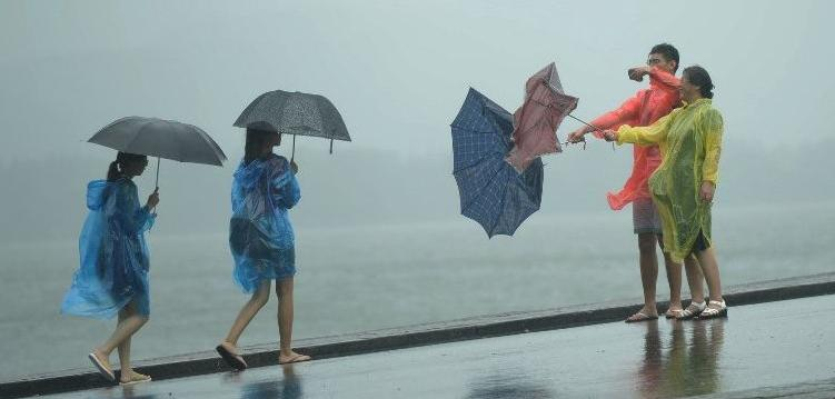 Two tourists take a photograph of their broken umbrella amid a heavy storm brought by typhoon Chan-hom in Hangzhou, east China's Zhejiang province on Jul 11, 2015. (Photo: AFP)