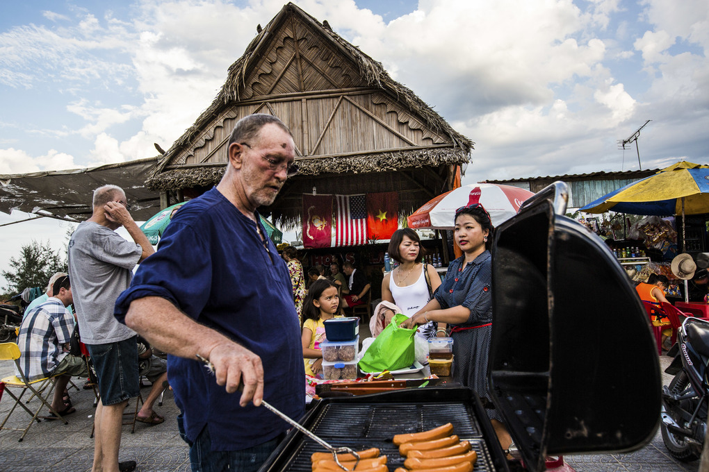 Larry Johnson, an American who moved to Vietnam, grills hot dogs at a Fourth of July party in Da Nang, Vietnam, July 4, 2015. A visit this week by the leader of Vietnam's Communist Party to the White House is seen in Vietnam and in the United States as a significant statement on the establishment of diplomatic relations. (Christian Berg/The New York Times)