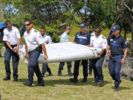 In this photo dated Wednesday, July 29, 2015, French police officers carry a piece of debris from a plane in Saint-Andre, Reunion Island. Photo: AP