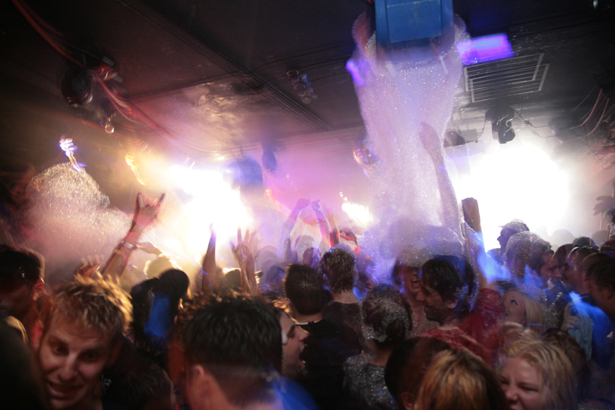 Dancing at a foam party; the blue object on the ceiling is a foam generator.