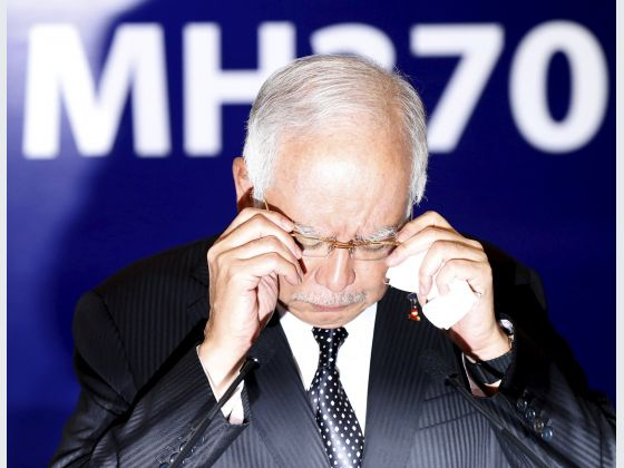 Malaysia's Prime Minister Najib Razak adjusts his glasses before confirming the debris found on Reunion Island is from missing Malaysia Airlines flight MH370 in Kuala Lumpur, Malaysia, August 6, 2015. Photo: Reuters