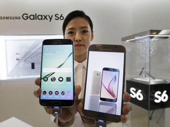 A model poses with the Samsung Electronics Galaxy S6, right, and Galaxy S6 Edge, left, smartphones during a launch event at the company's headquarters in Seoul, South Korea, on April 9, 2015. Photo: AP