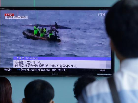 People watch a TV news program showing South Korean Coast Guard officers search for missing passengers after a fishing boat capsized in the water off north of the resort island of Jeju, at Seoul Railway Station in Seoul, South Korea, Sunday, Sept 6, 2015. Photo: AP